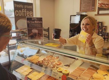 Bakery store assistant is giving a coffee and a leaflet to a customer in a Cooplands store
