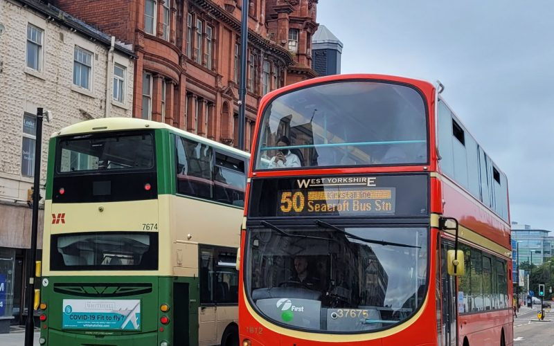 two buses, one red and one yellow and green