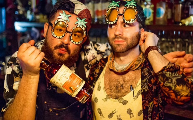 two men with party glasses on and with a bottle of win in their hands